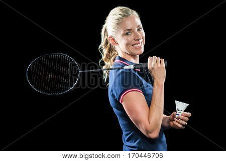 Badminton player holding racket and shuttlecock on black background