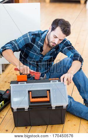 Man unpacking his tool box at home