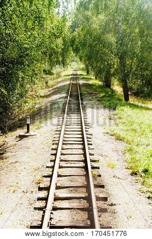 Narrow-gage railway rails at summer sunny day