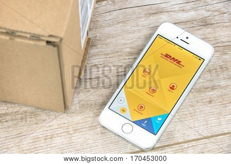 Krynica Poland - February 10 2017: DHL tracking shipment app on iPhone SE close to a parcel post. DHL is one of the largest postal shipping company on the world.