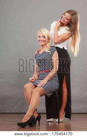 Fashionable style clothes concept. Woman wearing white top and long black shirt showing her leg standing next to sitting older female with short striped dress
