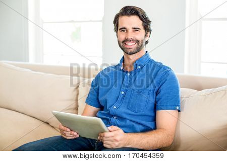 Portrait of handsome man using digital tablet while sitting on sofa at home