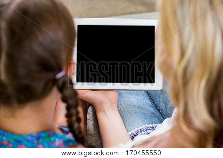 Rear view of mother and daughter with digital tablet at home