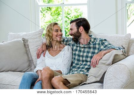 Romantic young couple looking at each other on sofa