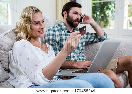 Woman holding debit card while sitting by man talking on phone with laptop at home