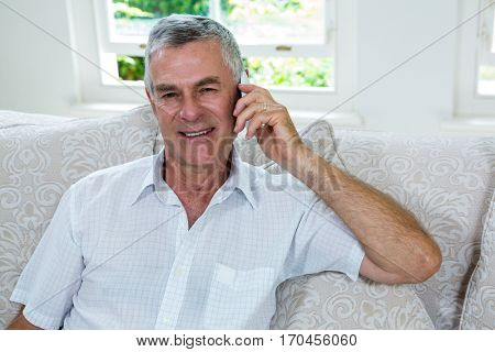 Portrait of happy senior man talking on mobile phone in sitting room