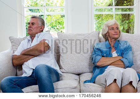 Annoyed senior couple looking away while sitting on sofa at home
