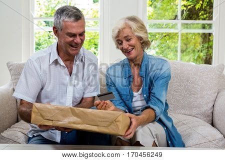 Happy senior couple holding parcel and debit card in sitting room at home