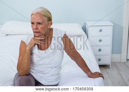 High angle view of upset senior woman sitting on bed in bedroom