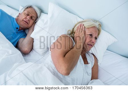 Senior woman blocking ears while man snoring in bedroom
