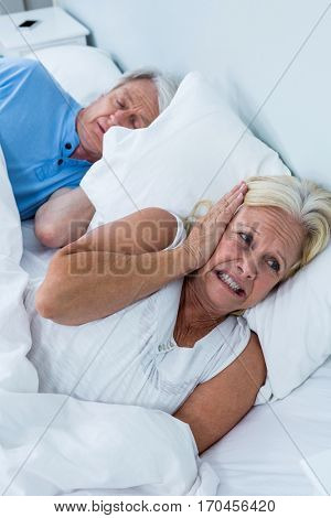 Senior woman covering ears while man snoring in bedroom