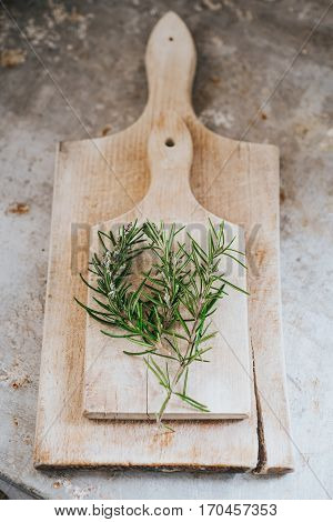 Rosemary branch on wooden board. Metal table.