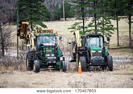 giant lawn mowers on a farm field