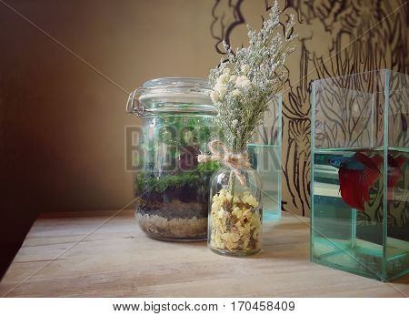 Terrarium with dried flower and small aquarium on table in coffee shop in Thailand.