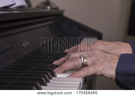 An image of a mature lady's hand playing the piano.