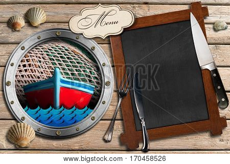 Empty blackboard for a seafood menu on a wooden background with sand silver cutlery and a porthole with a small boat and fishing net