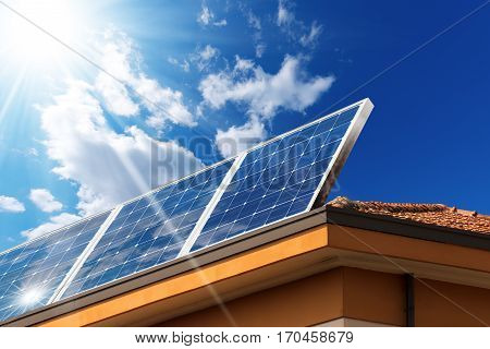 Close-up of a house roof with a solar panels on top on a blue sky with clouds and sun rays