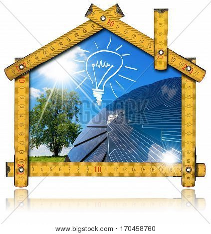 Wooden ruler in the shape of ecologic house with a solar panel light bulb blue sky tree and sun rays. Concept of ecological house