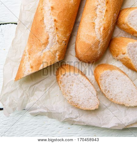 Breezy long baguette on paper at white wooden table