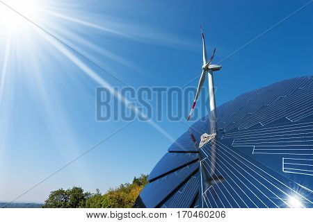 Close-up of a solar panel and a wind turbine on a clear blue sky with sun rays - Green energy concept