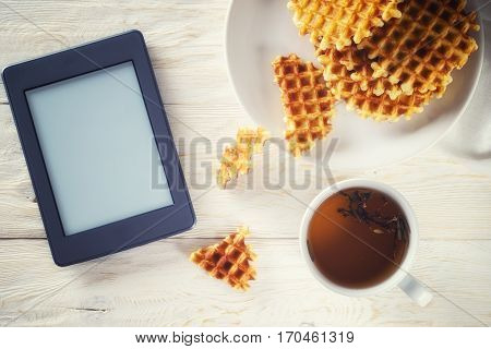 Cup of tea waffle and ebook. Copyspace