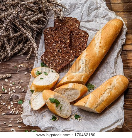 Sliced loaf and bread with grains on paper at table