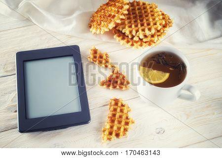 Cup of tea waffle and ebook closeup. Copyspace