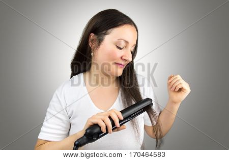 happy woman using flat iron to straigh her hair