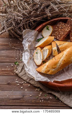 Wood table with plate of bread and wheat spikelets