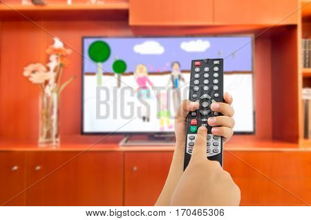 Hand of children holding television remote and watching cartoons and animated