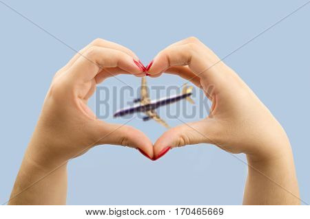 woman making the heart shape with her hands and the airplane in the middle