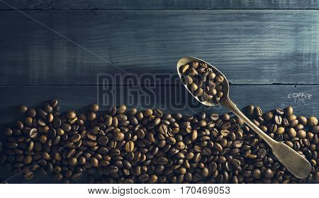 Coffee beans with old metal spoon on a dark blue wooden background. Copy space