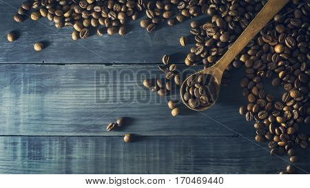 Coffee beans with old wooden spoon on a dark blue wooden background. Copy space