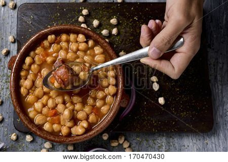high-angle shot of the hand of a man with a spoon and an earthenware bowl with spanish cocido madrileno, a stew typical of madrid with chickpeas, pork, bacon, chorizo and ham, on a rustic wooden table