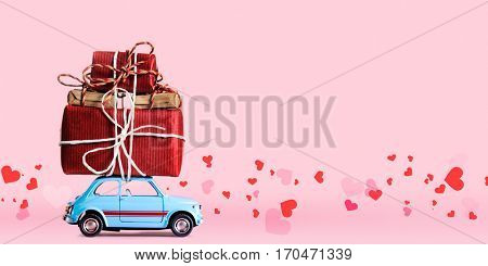 Blue retro toy car delivering gift box for Valentine's day on pink background with flying hearts
