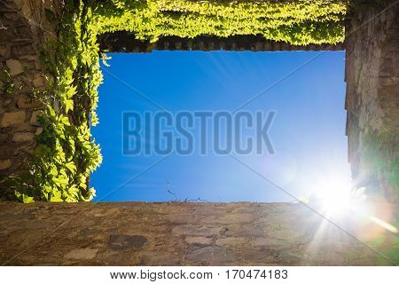 Upright shot from ground into blue sky framed by four walls showing sun as template