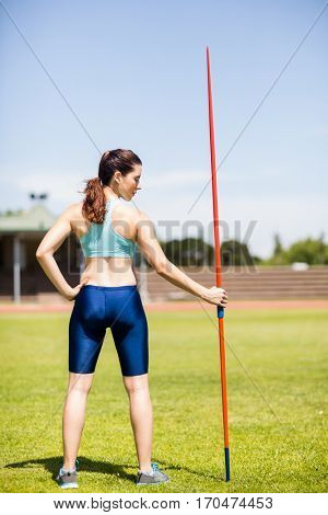 Rear view of female athlete holding a javelin in stadium on a sunny day
