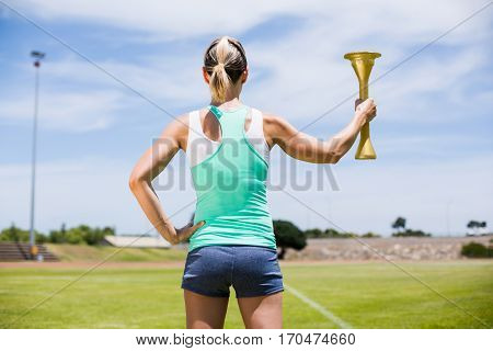 Rear view of happy female athlete holding a fire torch in stadium