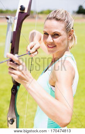 Happy female athlete practicing archery in stadium