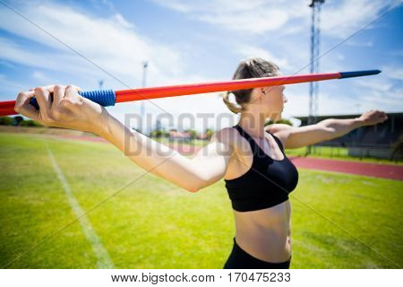 Female athlete about to throw a javelin in the stadium