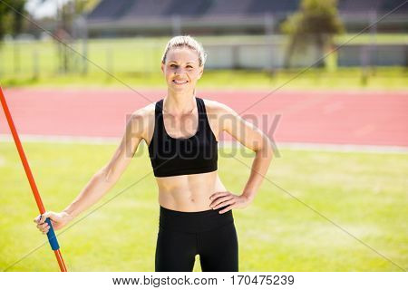 Portrait of happy female athlete holding a javelin standing in stadium