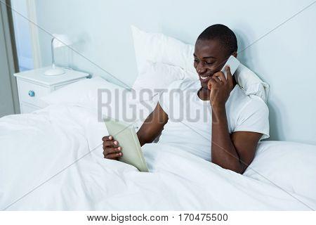Man looking at digital tablet while talking on phone in bedroom