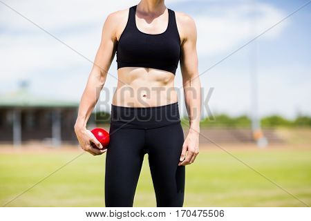 Mid section of female athlete holding a shot put ball in stadium