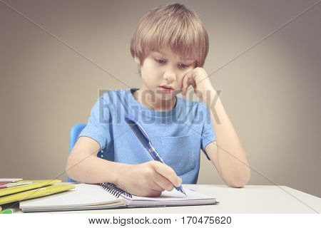 Boy writing on paper notebook. Boy doing his homework exercises. School, education concept