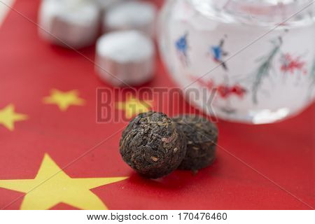 Compacted Puer tea blocks on a Chinese flag