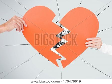 Hand of couple holding broken hearts against digital composite background