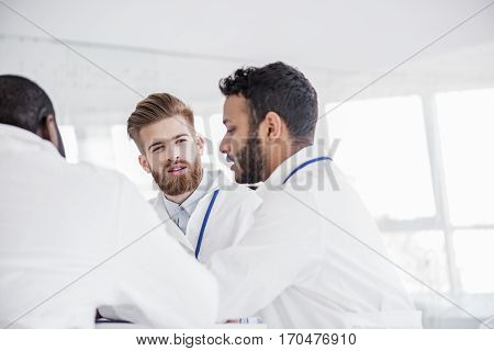 Cheerful bearded therapeutic negotiating with affiliates health status of client at meeting