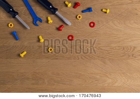 Kids toys tools: colorful screwdrivers, screws and nuts on wooden background. Top view. Flat lay.