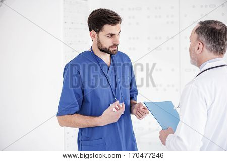 Outgoing attractive bearded medical man speaking with elderly doctor while standing opposite him at conference in apartment of clinic