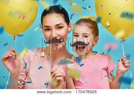 Funny family on background of bright blue wall. Mother and her daughter girl with paper accessories and balloons. Mom and child are holding paper mustache on sticks. Yellow, pink and turquoise colors.